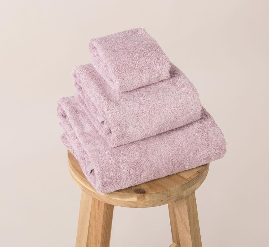 Tri roze peškira poređana po veličini na stolici