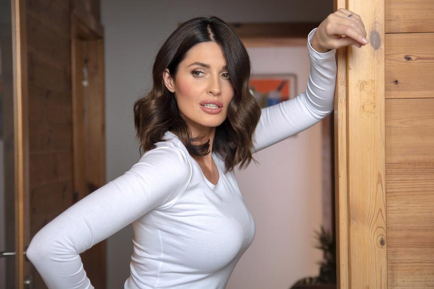 Žena pozira u beloj majici u sobi