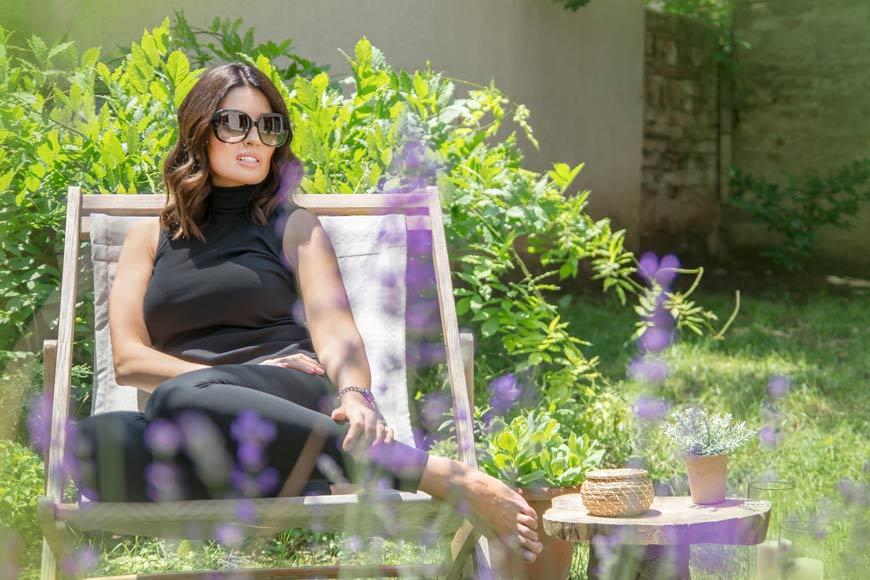 Žena sa naočarima sedi u dvorištu na ležaljci
