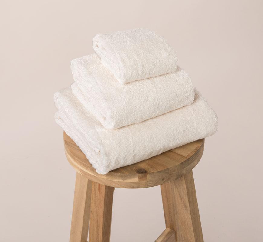 Tri pamučna peškira različitih veličina za ruke, telo i lice poređani jedan na drugi na stolici