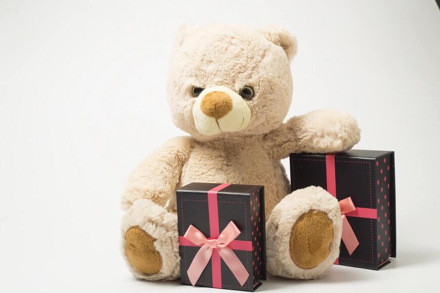 Plišani meda okružen sa dve ukrašene kutije za poklon